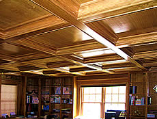 This cherry library includes bookcases, paneling, fireplace surround, and  a coffered ceiling